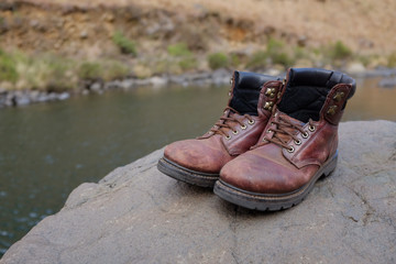 Old hiking boots beside river