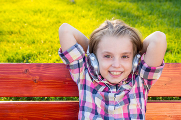 Very cheerful and funny little girl listening to music.
