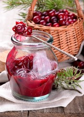 sauce of wild organic cranberries on a wooden table with berries