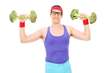 Nerdy guy exercising with two broccoli dumbbells