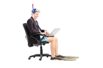 Businessman with a snorkel working on laptop