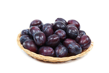 Fresh plums in a wooden basket on white background.
