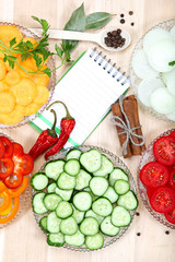 Vegetables, spices and notepad for recipes, on wooden table.