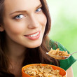 Woman eating muesli or cornflakes, outdoor
