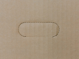 Corrugated cardboard paper background with perforated handle lin