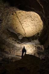 man silhouette in a huge dark cave