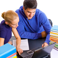 Young students with books and laptop studying