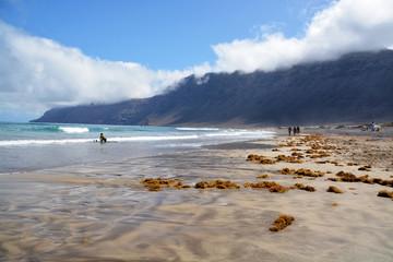 grupo caminando por la playa de famara en verano, lanzarote