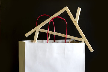 Shopping and buying a house concept in paper bag