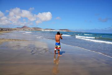 hombre fotografiando en la playa de famara de lanzarote