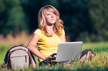 Beautiful girl sit with laptop on green grass