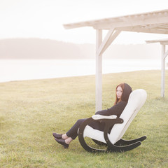 beautiful happy woman relax in chair on lake morning