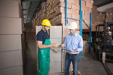 Warehouse worker loading up a pallet with manager