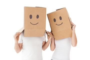 Couple wearing happy face boxes over heads