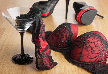 Panties in a martini glass on the background of  shoes and  bra