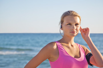 fitness woman on the beach in headphones