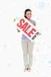 Composite image of young female holding a sales sign