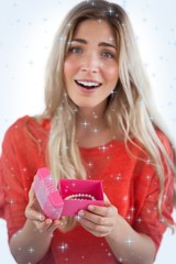 Composite image of surprised blonde woman opening gift