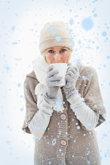 Composite image of mature woman in winter clothes holding mug