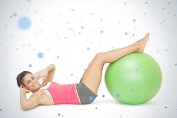 Smiling sporty brunette doing sit ups with exercise ball
