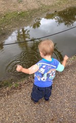 toddler boy throwing stones in puddle