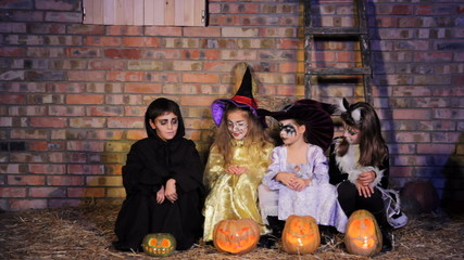 Children In Halloween Costumes With Pumpkins Sitting  Together