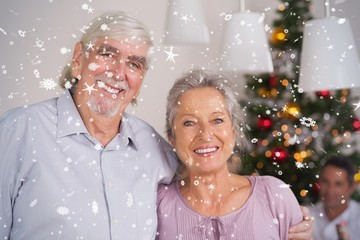 Composite image of happy grandparents at christmas