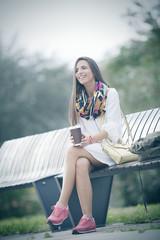 beautiful teenage student girl sitting in park