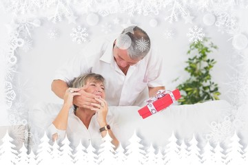 Composite image of old man hiding eyes his wife to give a gift