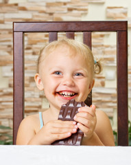 Little smiling girl with chocolate