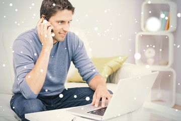Smiling man using cellphone and laptop in living room