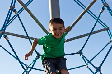 Kid having fun on the jungle gym at the playground