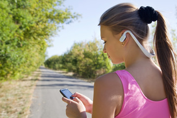 fitness young girl with phone and headphones