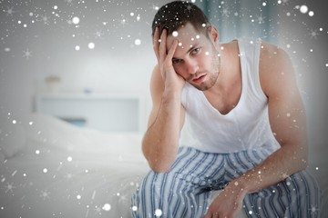 Composite image of depressed man sitting on his bed