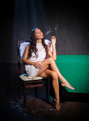 Smoking angel sits
