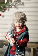 Small child presses a bottle with artificial snow
