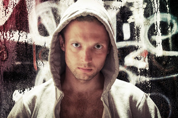 Young Caucasian man in hood, street artist portrait with grungy