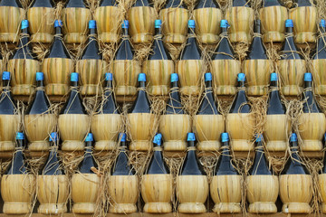 arranged many  chianti bottles in traditional pyramid on cart
