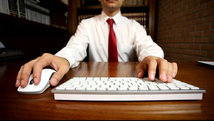 Businessman using a computer keyboard and a mouse