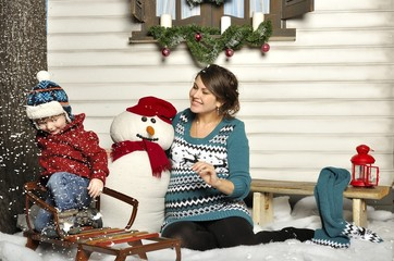 Young pregnant woman with the child about a snowman
