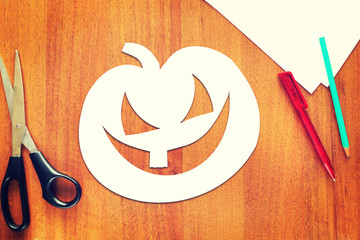 Halloween pumpkin cut out of paper lying on the table