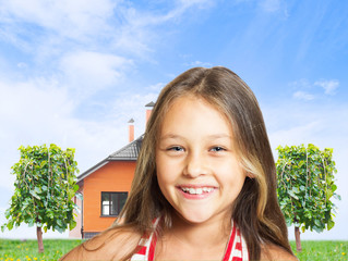 Positive little girl on a background of the sky and the house