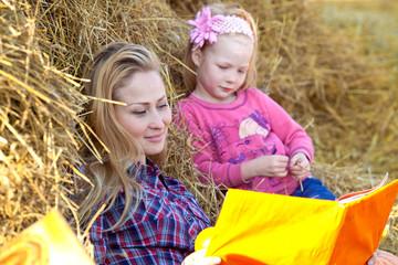Мама и дочь читают книгу на сеновале