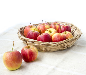 Small gala apple in basket on sack over white.