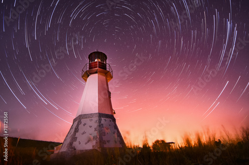 lighthouse with night sky at background stars trails - 70725561
