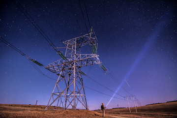 Electricity power poles on alone man -  night sky and stars