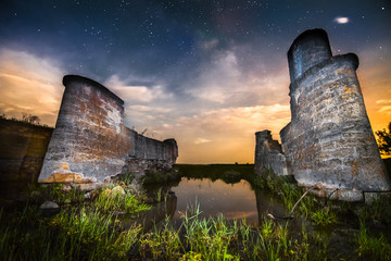 Old night castle wall ruins on lake reflections with stars sky a
