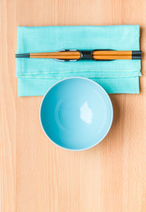 Empty rice bowl with bamboo chopsticks on wooden table.