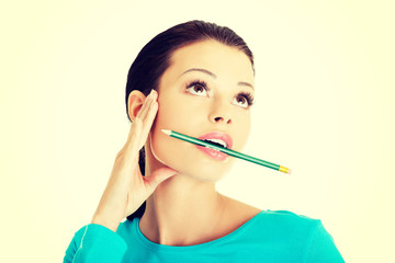 Thoughtful woman with pencil