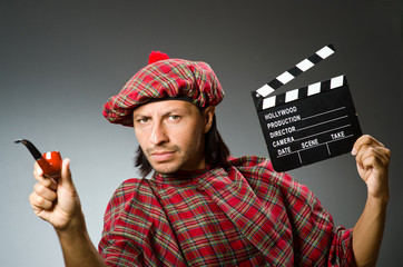 Funny scotsman with movie board and smoking pipe